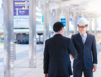 stock image of  portrait of male architect with safety hardhat greeting his partner. young man builder showing handshake. partnership concept.team