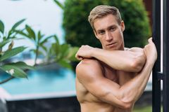 stock image of  portrait of sexy athletic man in white pants with naked torso resting in tropical garden