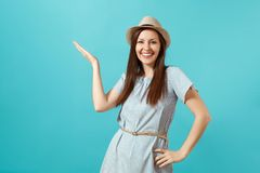 stock image of  portrait of smiling happy young elegant woman wearing dress, straw summer hat pointing hand aside on copy space isolated