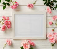 stock image of  poster frame mockup, top view, pink roses on white wooden background. holiday concept. flat lay. copy space