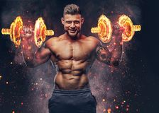 stock image of  handsome shirtless tattooed bodybuilder with stylish haircut and beard, wearing sports shorts, posing in a studio. fire