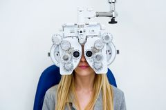 stock image of  pretty young woman doing eyesight measurement with optical phoropter in ophthalmology clinic