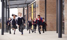 stock image of  primary school kids, wearing school uniforms and backpacks, running on a walkway outside their school building, front view