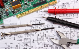 stock image of  printed circuit board. precision tools and cable of multimeter on diagram of electronics