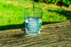 stock image of  process of pouring pure clear water into a glass from top, wooden log, green grass in the background, outdoors, health, hydration