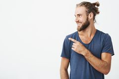 stock image of  profile of cheerful handsome man with fashionable hairstyle and beard smiling brightfully and pointing at free space for