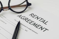 stock image of  property or real estate, house and home concept, pen and eyeglasses on rental agreement printed document, ready to sign contract