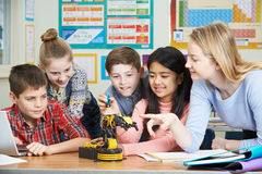 stock image of  pupils and teacher in science lesson studying robotics