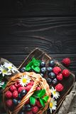 stock image of  raspberries and blueberries in a basket with chamomile and leaves on a dark background. summer and healthy food concept