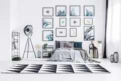 stock image of  real photo of a bed standing between a lamp and a chair in a bright bedroom interior with black and white rug and posters on a wa