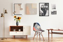 stock image of  real photo of bright eclectic living room interior with many posters, colorful chair, wooden cupboard with flowers and coffee tabl