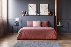 stock image of  real photo of a simple bedroom interior with dirty pink bedding