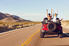 stock image of  rear view of friends on road trip driving in convertible car