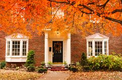 stock image of  red brick house entrance with seasonal wreath on door and porch and bay windows on autumn day with leaves on the ground and hydrag