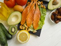 stock image of  red fish, avocado, nuts antioxidant lemon protein ingredient on a wooden background