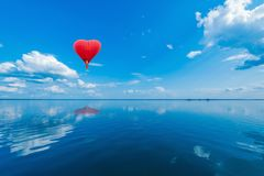 stock image of  red hot air balloon in the shape of a heart.