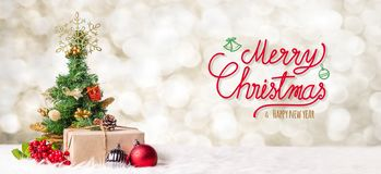 stock image of  red merry christmas and happy new year handwriting with xmas tree and gift box at blur bokeh light background,winter holiday