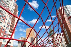 stock image of  the red ropes in the form of web houses on the background in the backlight of the setting sun. children sport hobbies urban enviro