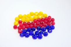 stock image of  red, yellow and blue beads on a white background. for crafts and hobbies.