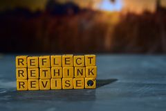 stock image of  reflect - rethink - revise on wooden blocks. cross processed image with bokeh background