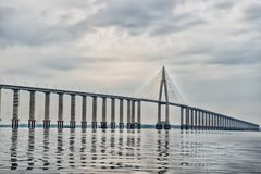 stock image of  road passage over water on cloudy sky. bridge over sea in manaus, brazil. architecture and design concept. travel destination and