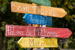 stock image of  road sign to exotic cities - saint tropez, tenerife, palma de mallorca, miami