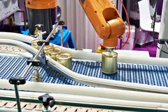 stock image of  robotic arm and cans on conveyor