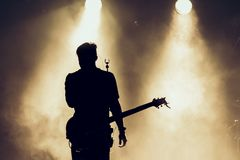 stock image of  rock band performs on stage. guitarist plays solo. silhouette of guitar player in action on stage in front of concert crowd. close