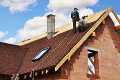 stock image of  roofers lay and install asphalt shingles. roof repair with two roofers. roofing construction with roof tiles, asphalt shingles.