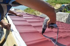 stock image of  roofing contractors installing metal roof tile for roof repair. roofing construction