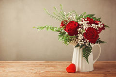 stock image of  rose flower bouquet and heart shape box on wooden table with copy space
