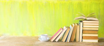 stock image of  row of old books and a cup of coffee on a rustic book shelf.