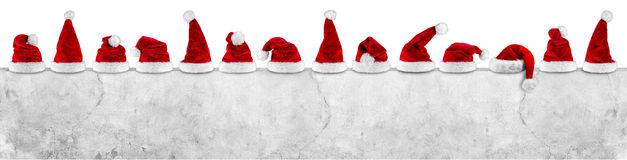 stock image of  row of red white santa claus christmas xmas hat on empty concrete wall