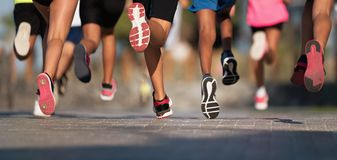 stock image of  running children, young athletes run in a kids run race,running on city road
