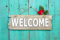 stock image of  rustic welcome sign with red flower hanging on distressed antique green door