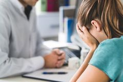 stock image of  sad patient visiting doctor. young woman with stress or burnout getting help from medical professional or therapist.