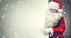 stock image of  santa claus pointing on blank advertisement banner background with copy space