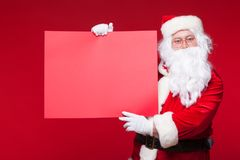 stock image of  santa claus pointing in blank advertisement banner isolated on red background with copy space red leaf