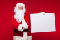 stock image of  santa claus pointing in blank advertisement banner on red background with copy space