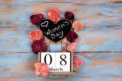 stock image of  save the date block calendar for international womens day, march 8, with chalkboard, next to roses flowers, on blue