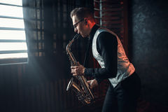 stock image of  saxophonist playing jazz melody on saxophone