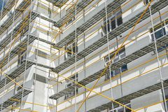 stock image of  scaffolding near a new house, building exterior, construction and repair industry, white wall and window, yellow pipe