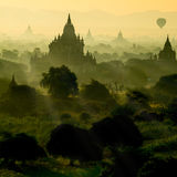stock image of  scenic sunrise with silhouette balloons above ruin pagoda in bagan, myanmar.