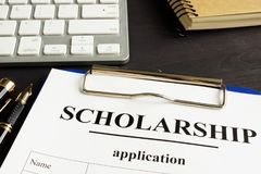 stock image of  scholarship application and money for education on a table.