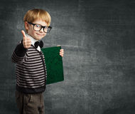 stock image of  school child in glasses thumbs up, kid boy hold book