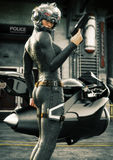 stock image of  science fiction female police officer posing in front of her jet bike ,wearing helmet and uniform
