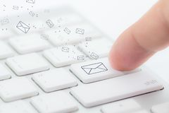 stock image of  sending email. gesture of finger pressing send button on a computer keyboard.