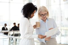stock image of  senior female executive discussing report with young mixed race