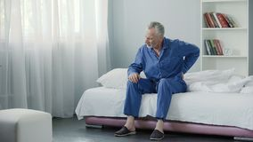stock image of  senior male suffering sharp back pain, sick person getting up from bed, morning