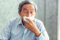 stock image of  senior man having sickness and sneezing into tissue, healthcare